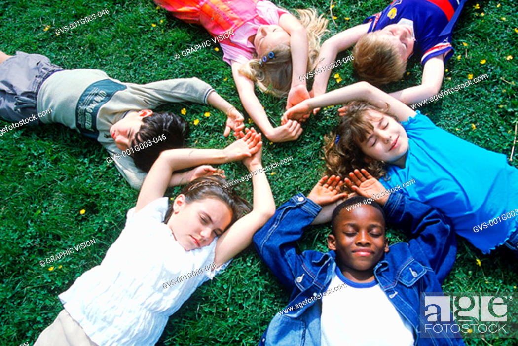 Stock Photo: Young children lying on the lawn in a circle.