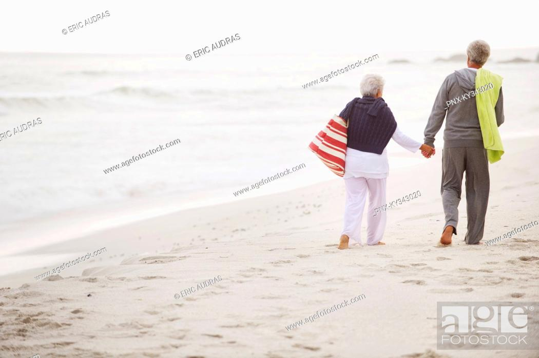 Stock Photo: Rear view of a senior couple walking on the beach.