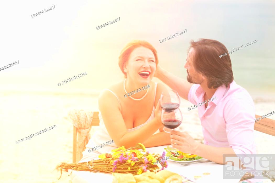 Photo de stock: Toned picture of happy couple spending free time all together in restaurant or cafe. Handsome man and beautiful woman having lunch with red wine.