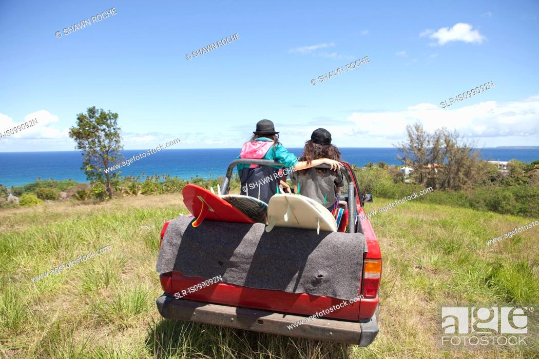 Stock Photo: Off road vehicle driving toward beach with two women in back.