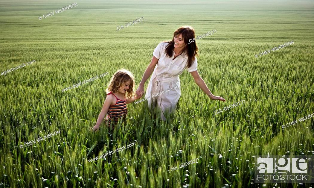 Stock Photo: Woman and child walking in wheat-field.