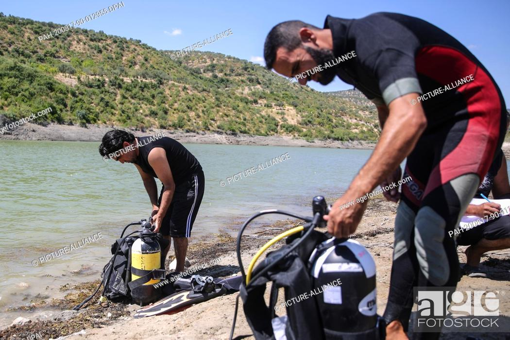 Stock Photo: 17 August 2020, Syria, Idlib: Members of the Syrian civil defence, also known as the White Helmets, prepare diving gear during a scuba diving training session.