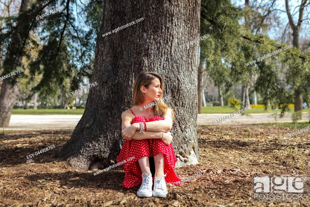 Stock Photo: Young serious blond woman siting near tree with red long dress.