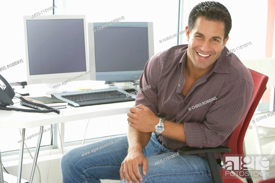 Stock Photo: Businessman smiling by computers in office portrait.