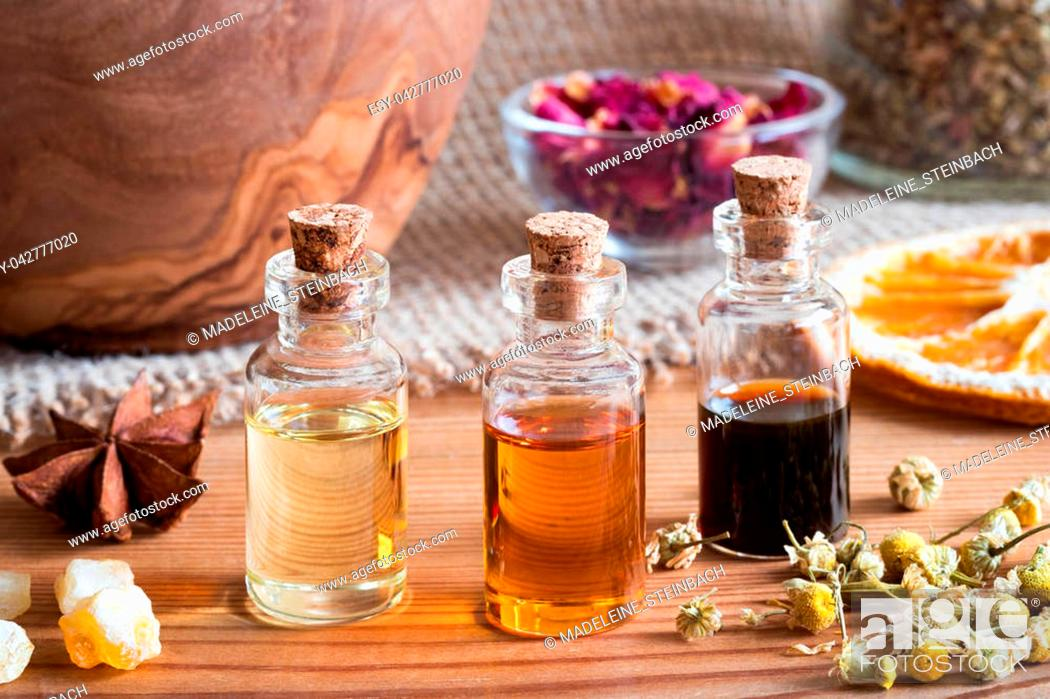 Stock Photo: Bottles of essential oil with star anise, frankincense, dried chamomile flowers and dried orange slices.