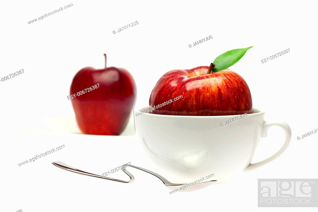 Imagen: apple in a cup and spoon isolated on white.