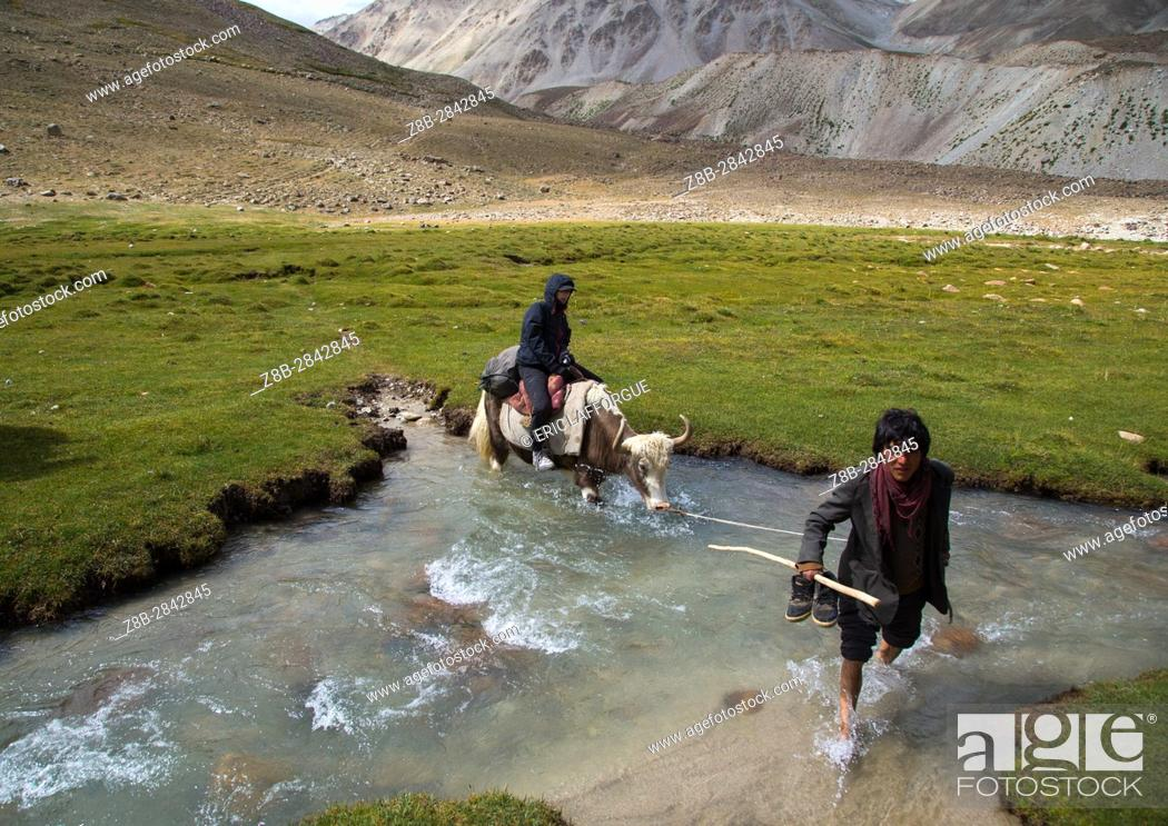 Stock Photo: Tourist riding a yak crossing a river during a treck, Big pamir, Wakhan, Afghanistan.
