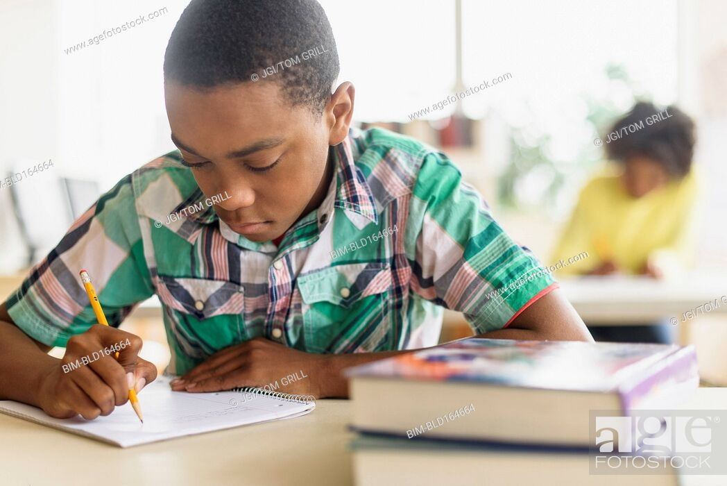Stock Photo: Black student writing in classroom.