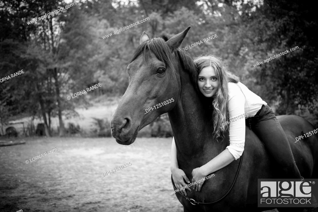 Stock Photo: A young woman, a horse trainer and rider, sits and embraces her horse and poses for the camera; British Columbia, Canada.