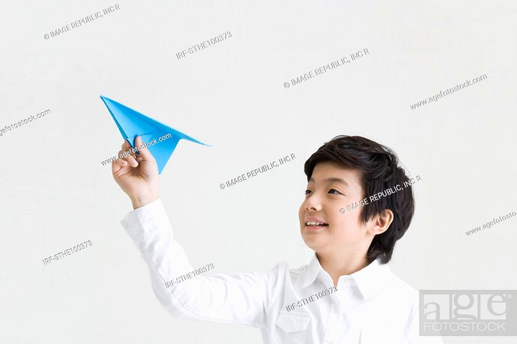 Stock Photo: boy holding a paper airplane.