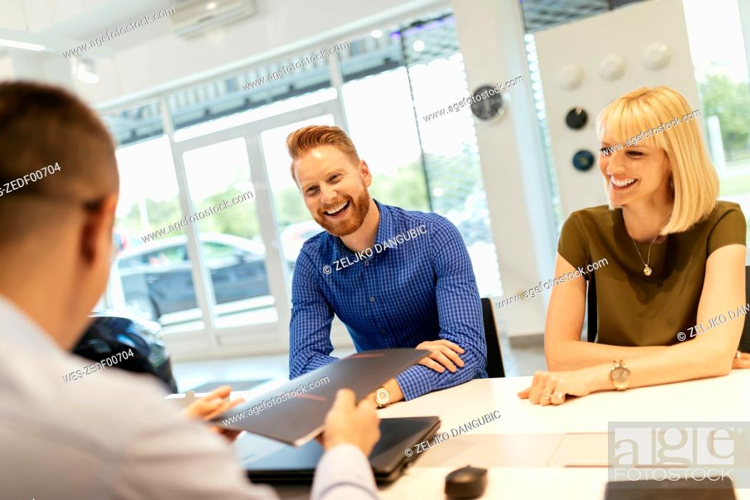 Stock Photo: Salesperson advising couple in car dealership.