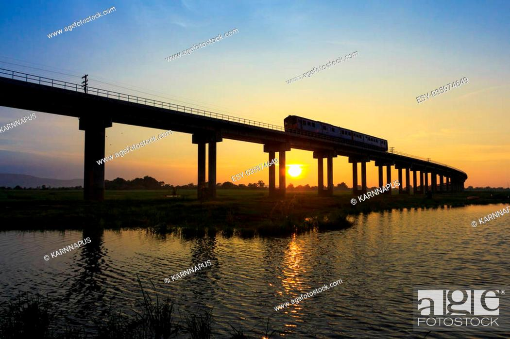 Stock Photo: A train is crossing bridge at Pa Sak Jolasid Dam, Thailand in sunset time.