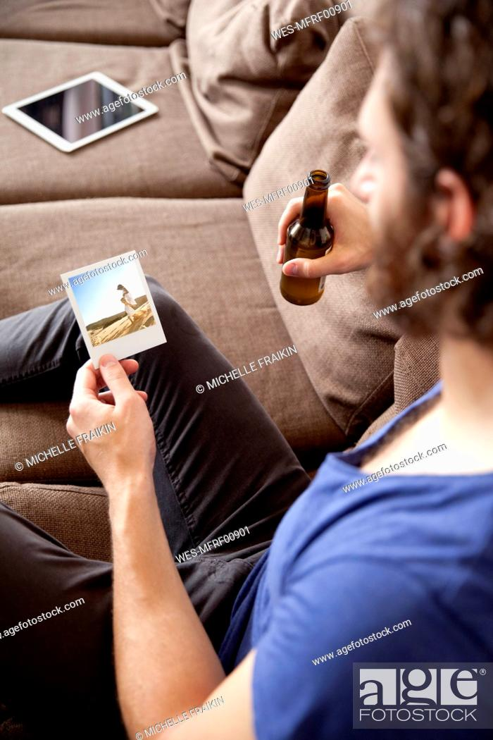Imagen: Man sitting on couch with beer bottle looking at instant photo.