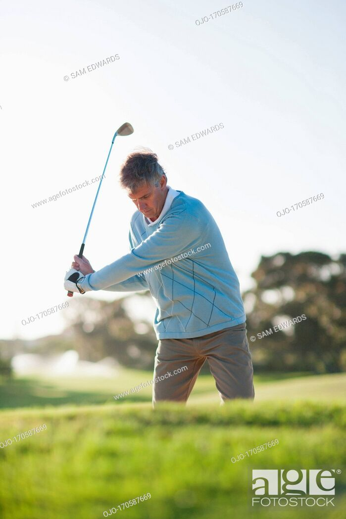 Stock Photo: Man playing golf in sand trap.