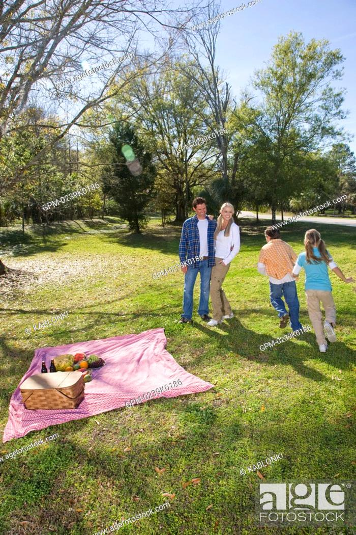 Stock Photo: Young happy family playing in park around picnic blanket.