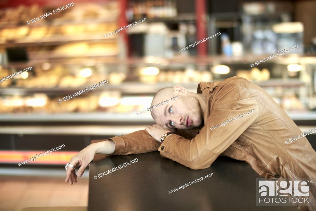 Stock Photo: man laying on table at supermarket bakery.