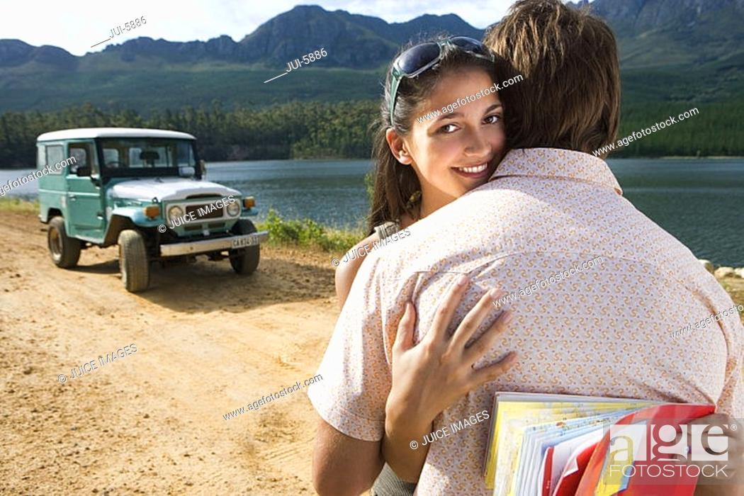 Stock Photo: Young couple embracing near parked jeep on dirt track beside lake, woman smiling, portrait.