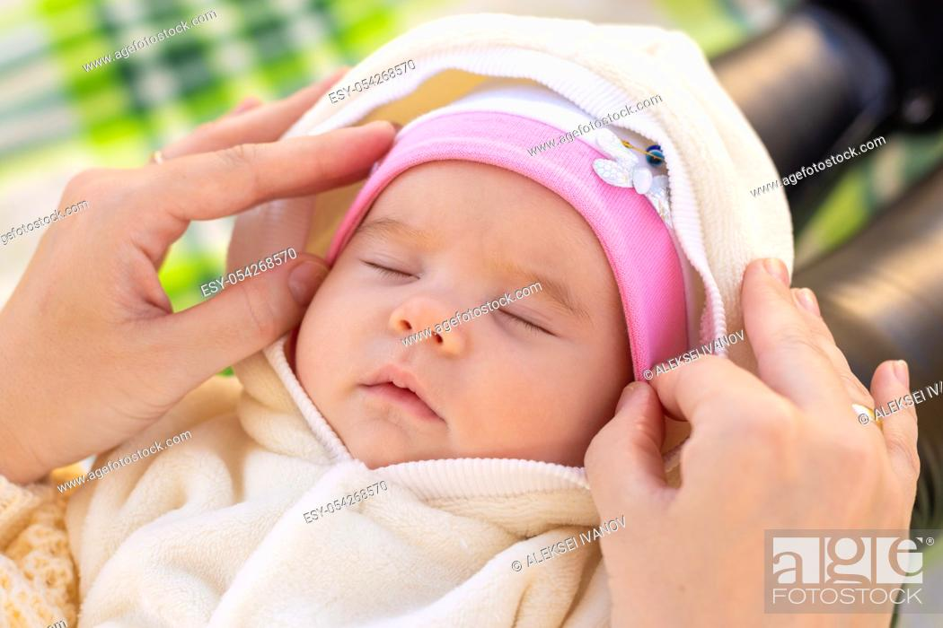 Stock Photo: Mom fixes the cap of a two-month-old baby.