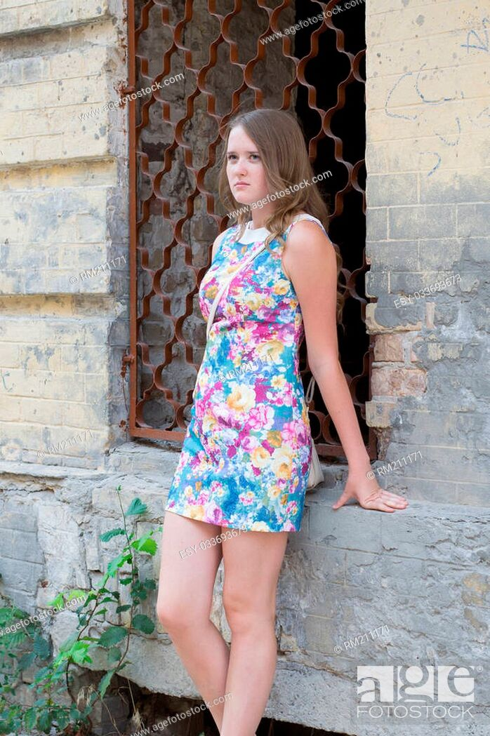 beautiful girl near the wall of an abandoned house in bright multi