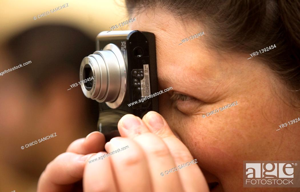 Stock Photo: A blind female student takes a picture during a photography workshop for the blind and visually impaired, imparted by Sight of Emotion organization in Mexico.