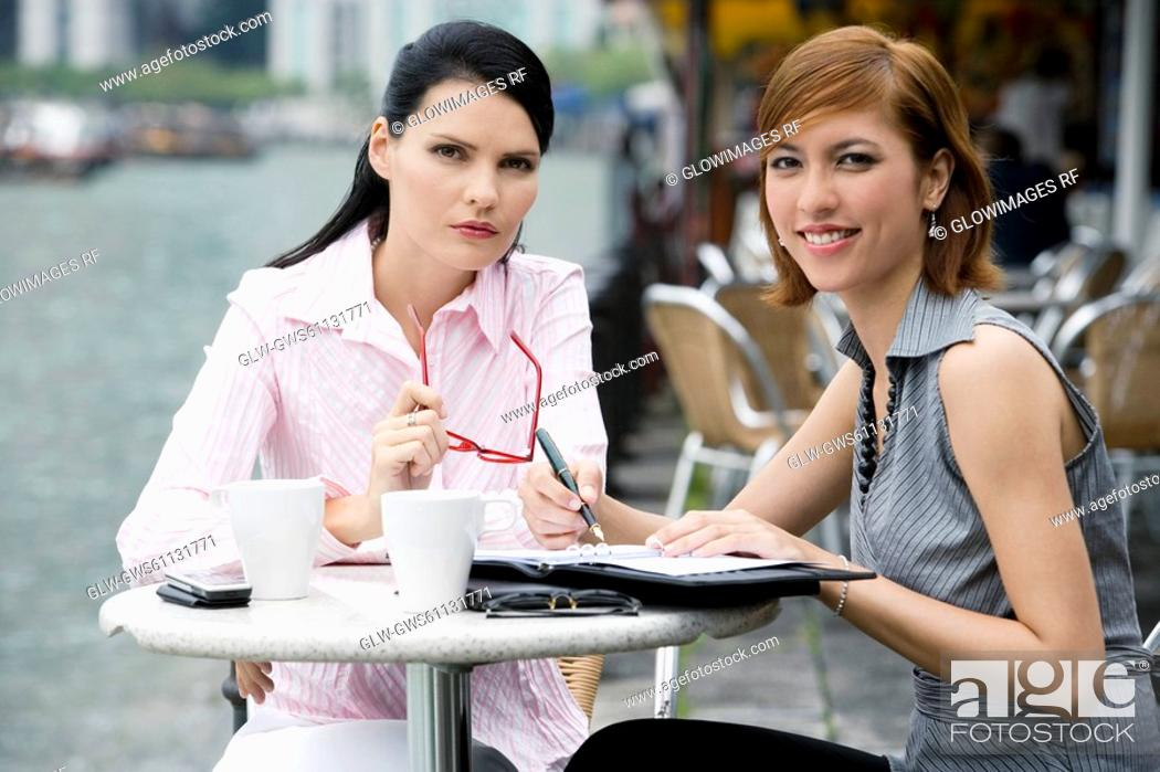 Stock Photo: Portrait of two businesswomen sitting at a sidewalk cafe.
