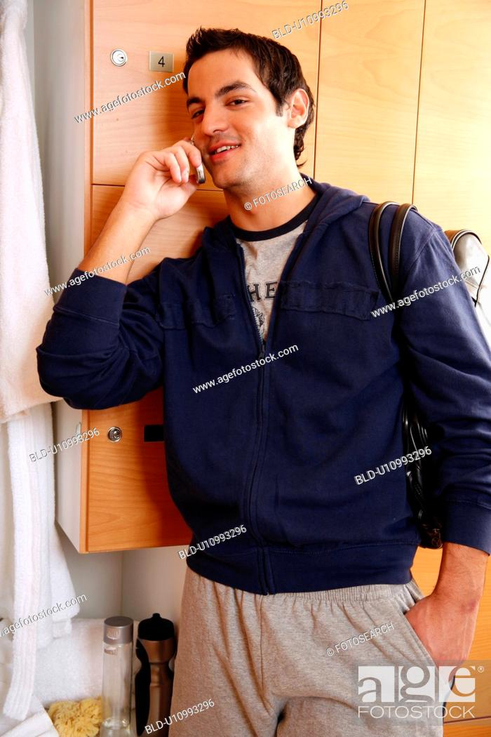 Stock Photo: Man in locker room after work out talking on cell phone.