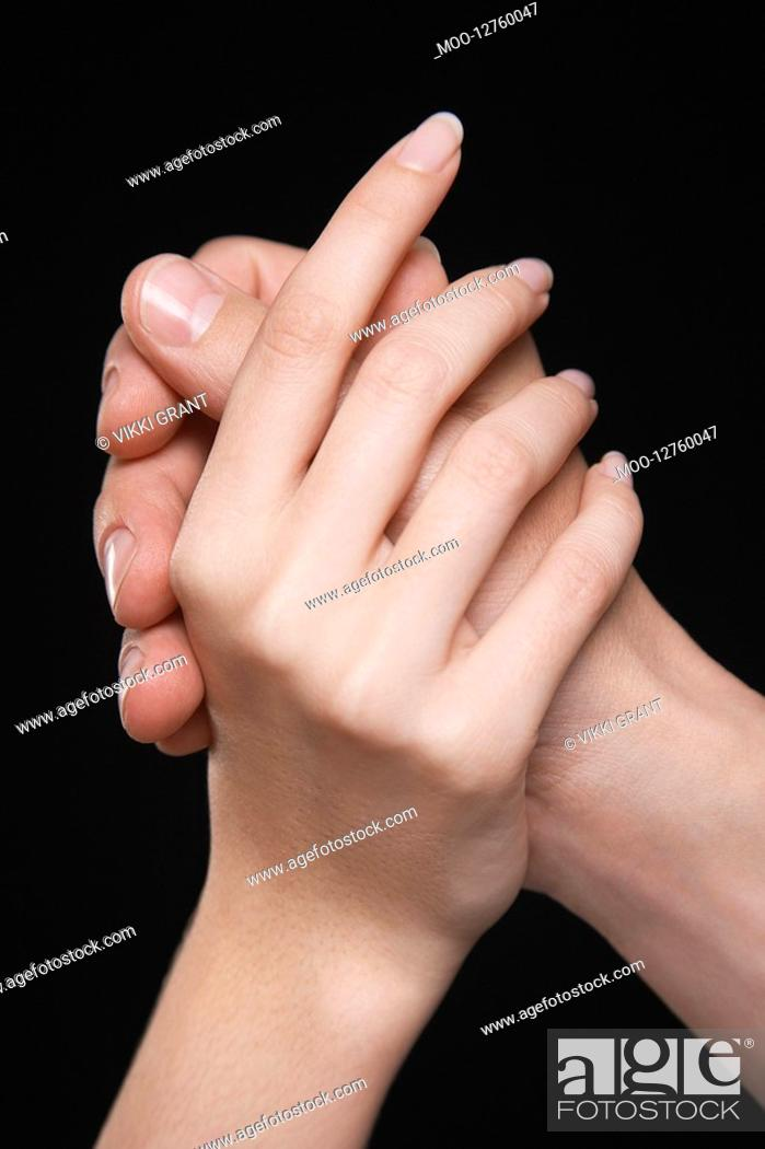 Stock Photo: Young couple holding hands arms raised together close-up of hands.