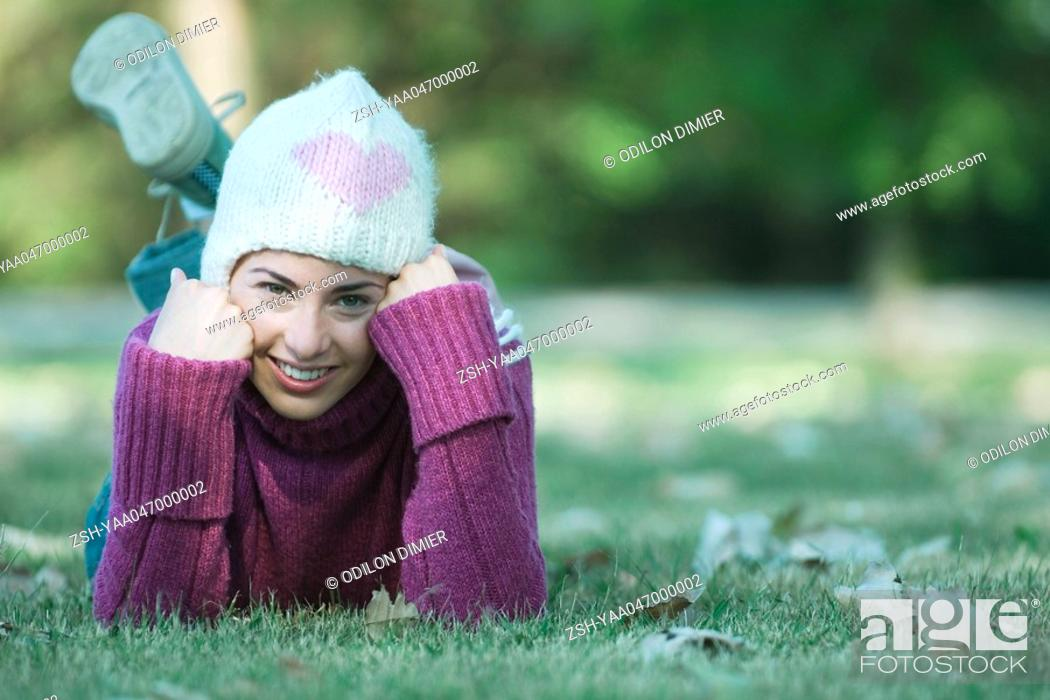 Stock Photo: Young woman lying on grass, wearing knit hat and sweater.