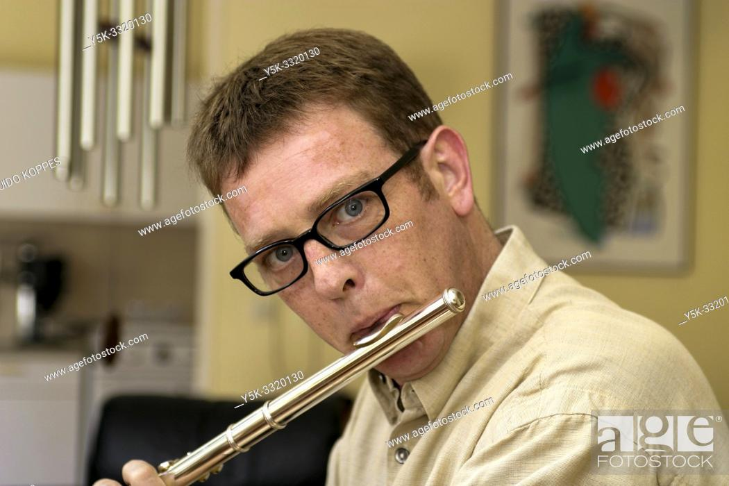 Stock Photo: Tilburg, Netherlands. Portrait of a 39 year old male wearing glasses and playing the flute. This music instrument is usually associaled with women.