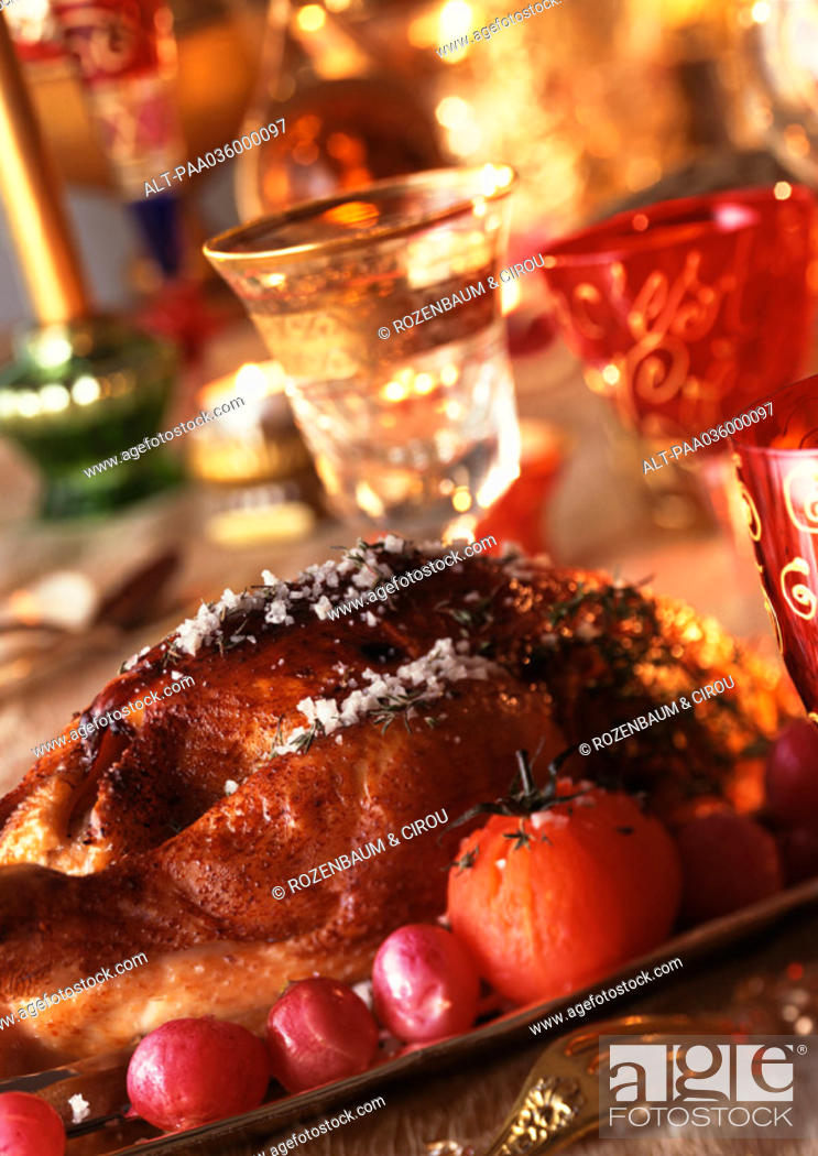 Stock Photo: Roast chicken with vegetables, wine glasses in background, close-up.