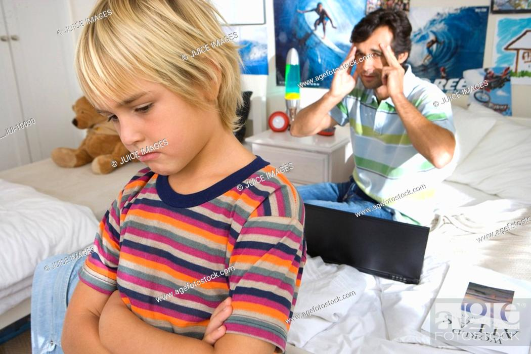 Stock Photo: Father reprimanding son 6-8 in bedroom, close-up of boy.