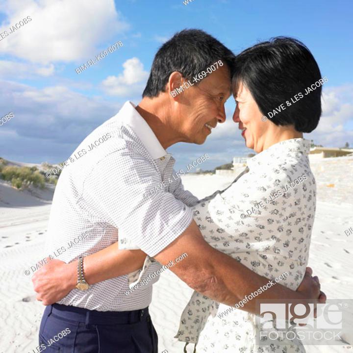Stock Photo: Senior Asian couple hugging at the beach, Perth, Australia.