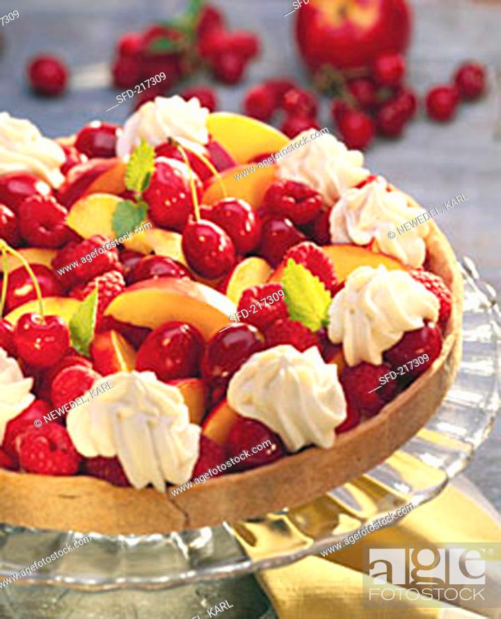 Stock Photo: Colourful fruit tart with cream rosettes & lemon balm leaves.