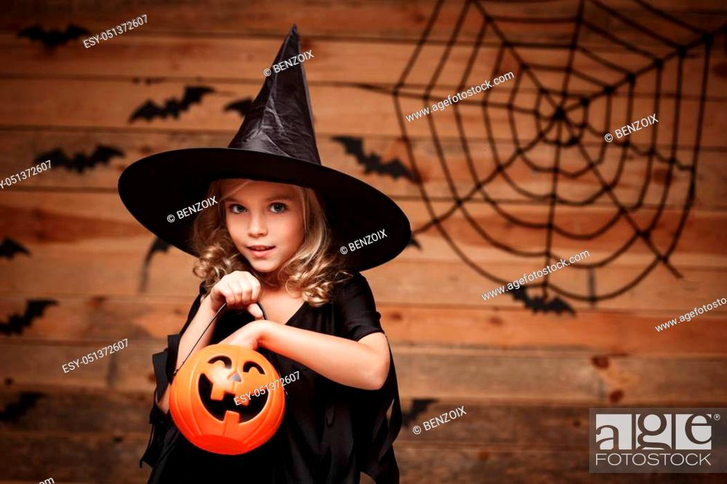 Stock Photo: Halloween Witch concept - little caucasian witch child enjoy with halloween candy pumpkin jar. over bat and spider web background.