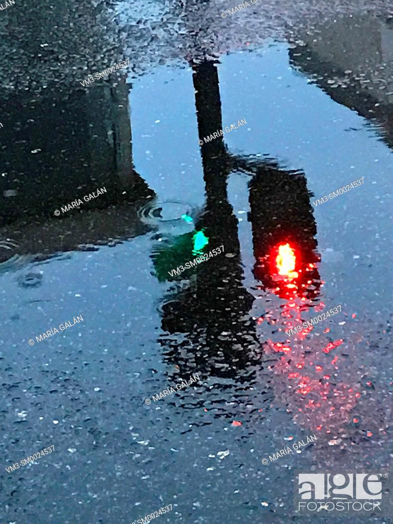 Imagen: Traffic light reflected on the water of a puddle in a rainy day.