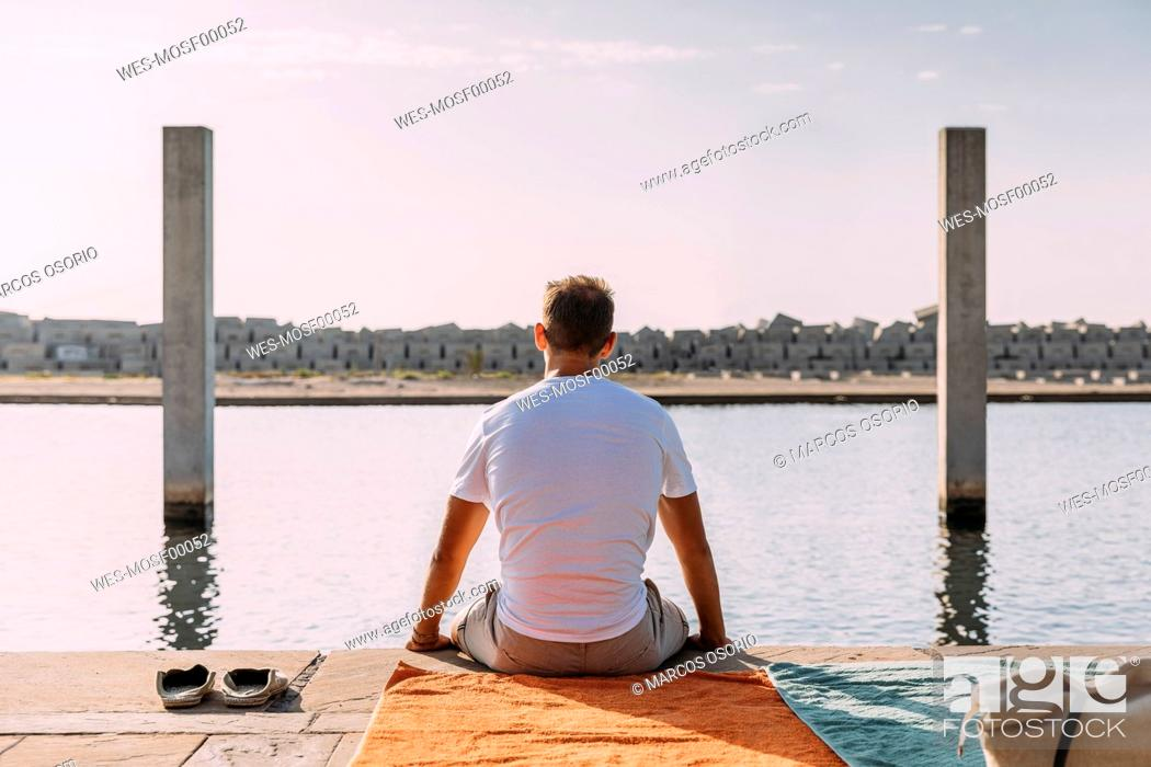 Photo de stock: Young man sitting on a pier at the sea.