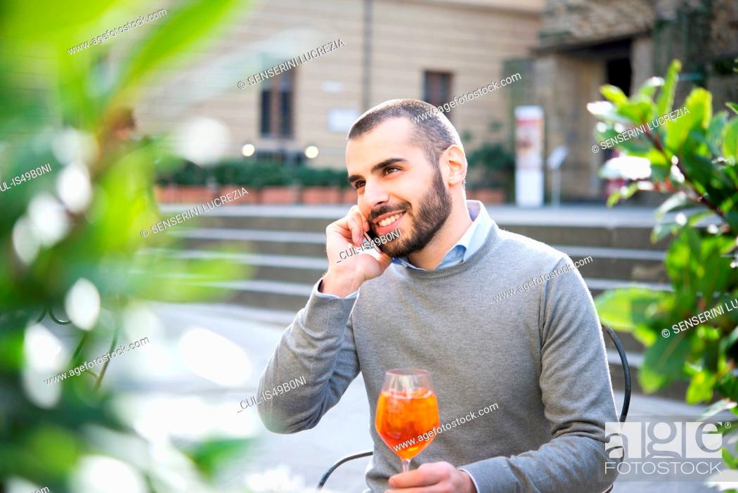 Stock Photo: Young man sitting outside bar, holding drink, using smartphone.