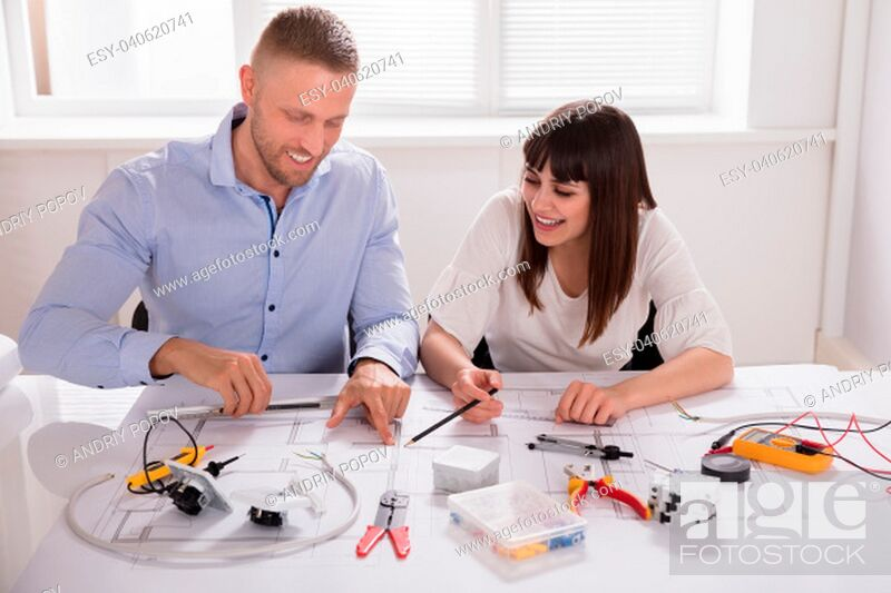 Stock Photo: Smiling Young Male And Female Architect Working On Blueprint In Office.
