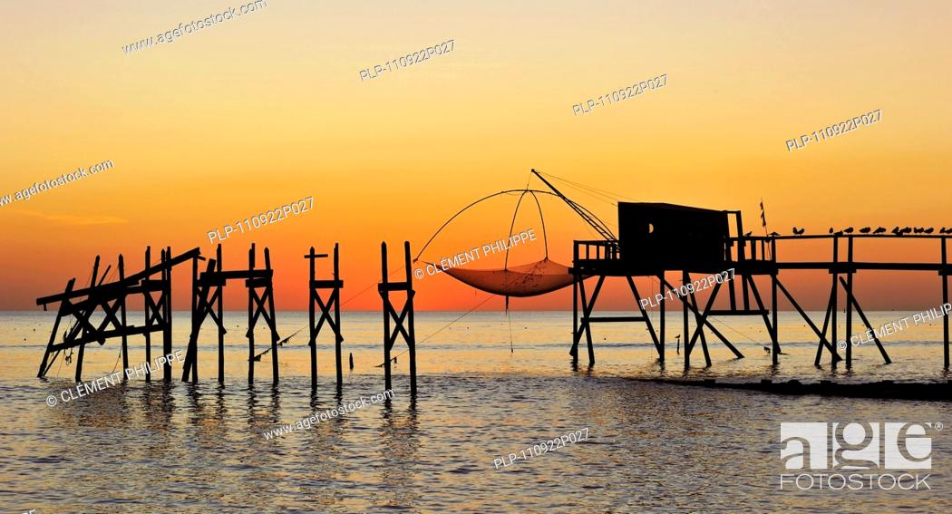 Stock Photo: Traditional carrelet fishing hut with lift net on the beach at sunset, Loire-Atlantique, France.
