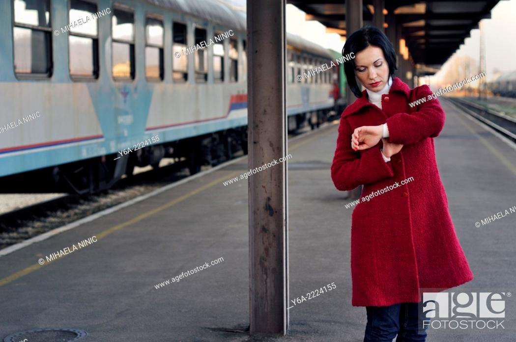 Stock Photo: Mid adult looking at her wristwatch at the train station.