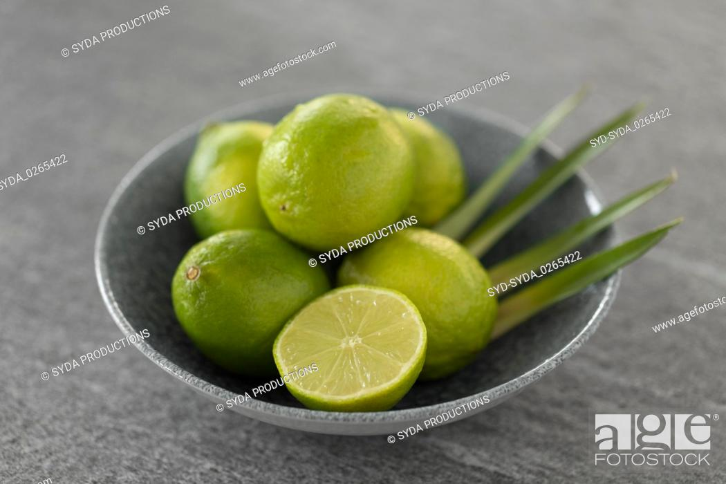 Stock Photo: close up of limes in bowl on slate table top.