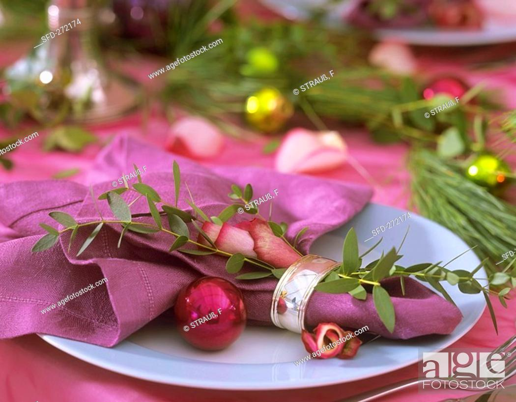 Stock Photo: Place-setting with Eucalyptus, rose petals and tree baubles.