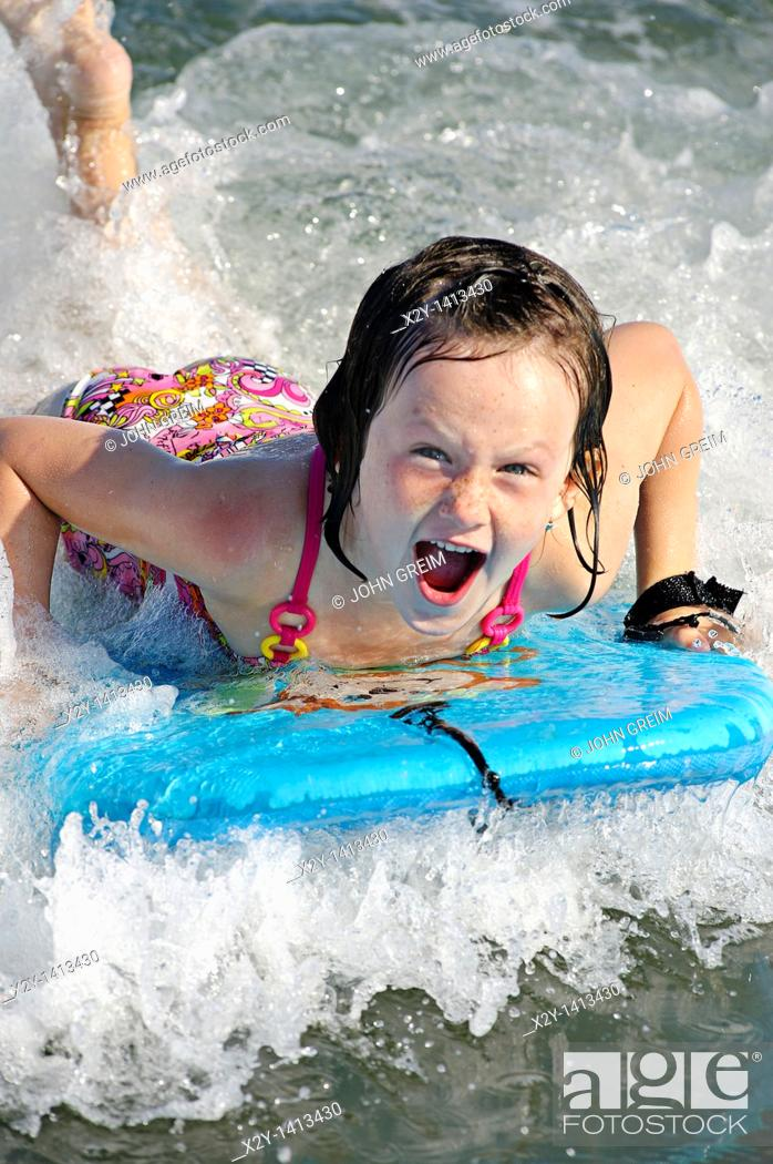 Stock Photo: Girl on a wave board enjoying the ride, Ocean City, New Jersey, USA.