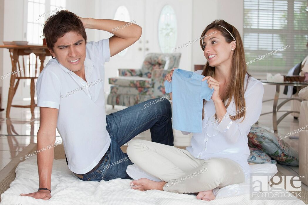 Stock Photo: A man looking uncertain at the blue baby shirt his girlfriend is showing him.