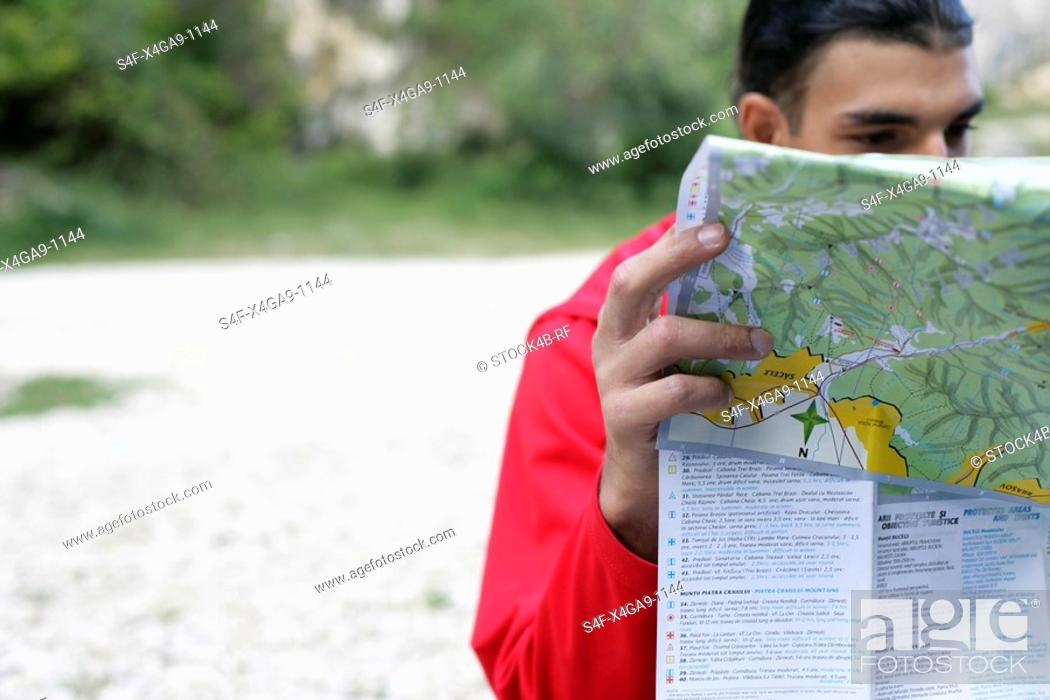 Stock Photo: Man is studying a map.