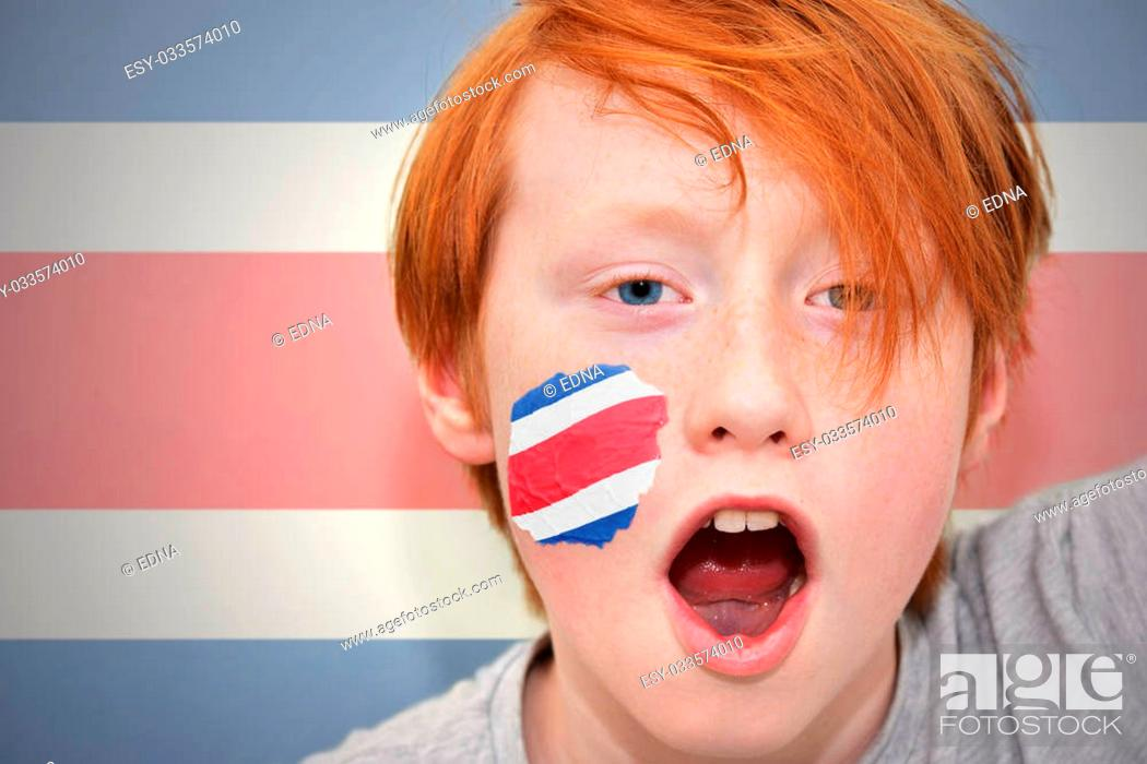Imagen: redhead fan boy with costa rican flag painted on his face. on the costa rican flag background.