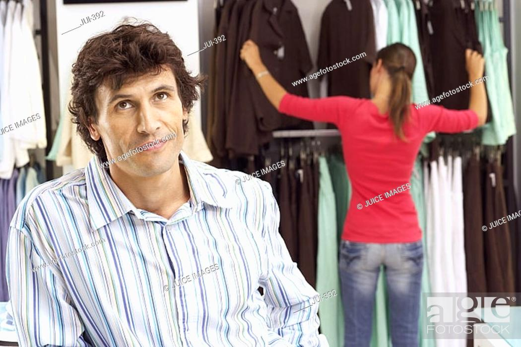 Stock Photo: Bored man waiting in clothes shop, girlfriend choosing tops from rail in background, focus on foreground.