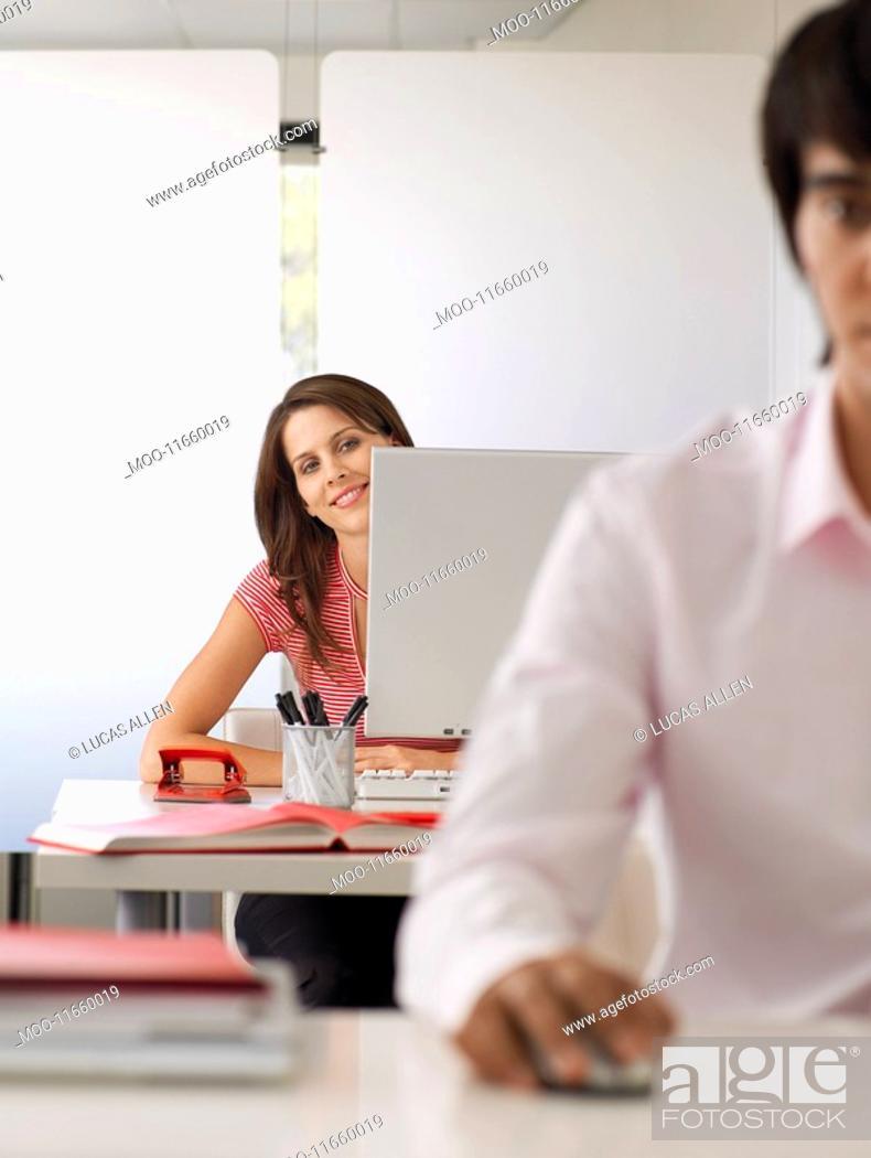 Stock Photo: Businesswoman at desk half length.