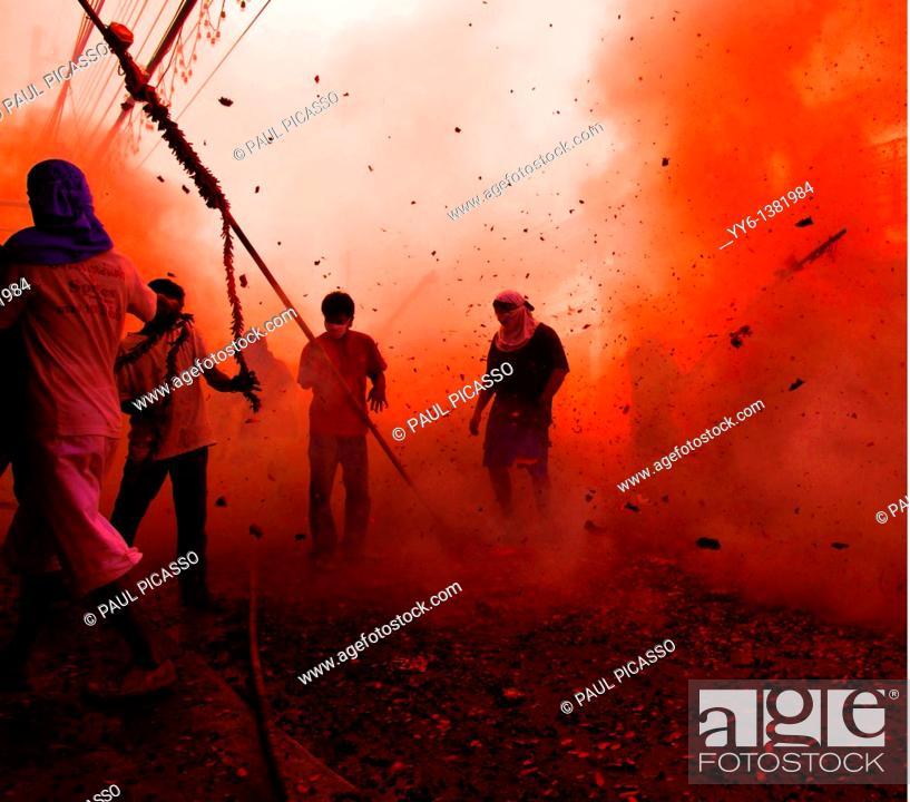 Stock Photo: firework madness , devotee's come under fire during a temple run , firework madness , phuket vegetarian festival , phuket, thailand.