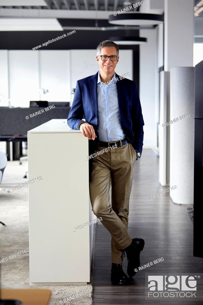 Imagen: Portrait of smiling businessman in office.